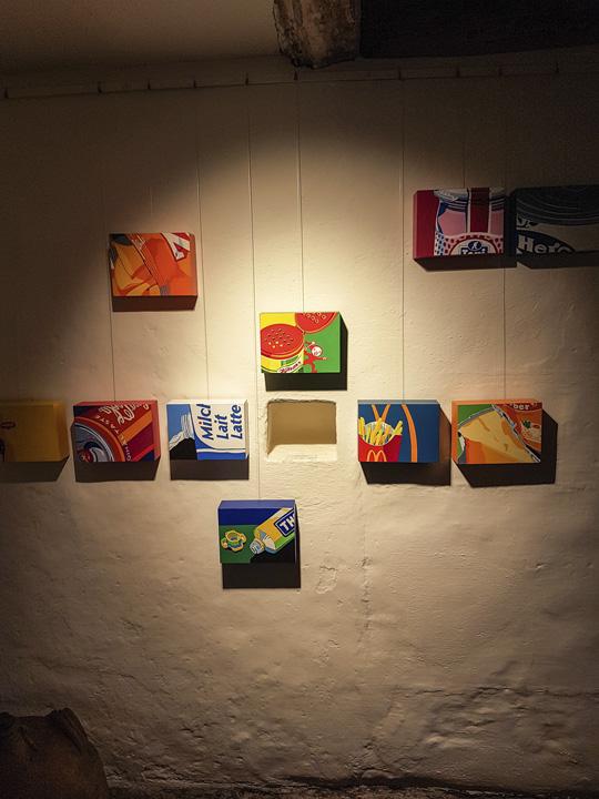 Diverse Holzkörper bemalt mit Sujets von Lebensmittelmarken, z.B Thomy Mayonnaise