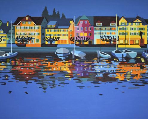 Hafenansicht mit Booten und beleuchteter Häuserzeile bei Dunkelheit